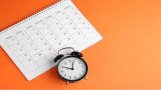 desk calendar and clock on orange background